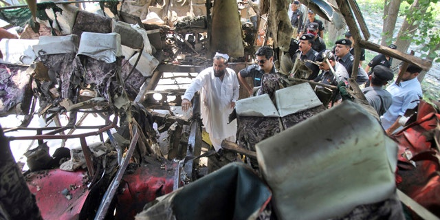June 8, 2012: Pakistani police officers check the wreckage of a bus that exploded when a bomb planted in it went off on the outskirts of Peshawar, Pakistan.