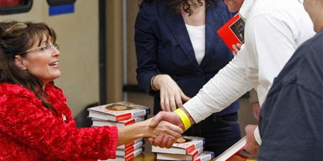 Sarah Palin shakes hands while signing books inside the Walmart in Spirit Lake, Iowa, Thursday, Dec. 2, 2010. (AP Photo/The Register, John Gaps III)