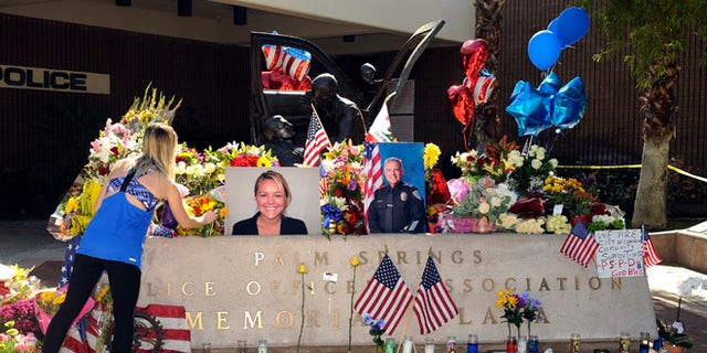 """Kimberleigh Funkey, from Palm Springs, Calif., lays flowers by photos of slain Palm Springs police officers Lesley Zerebny and Jose """"Gil"""" Gilbert Vega, in front of the police station in Palm Springs, Calif., Sunday, Oct. 9, 2016. (AP Photo/Rodrigo Peña)"""