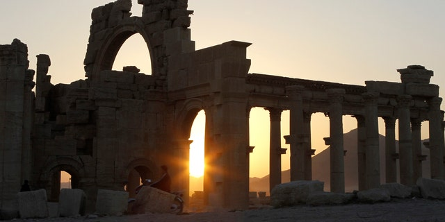 The sun sets behind ruined columns at the historical city of Palmyra, in the Syrian desert.