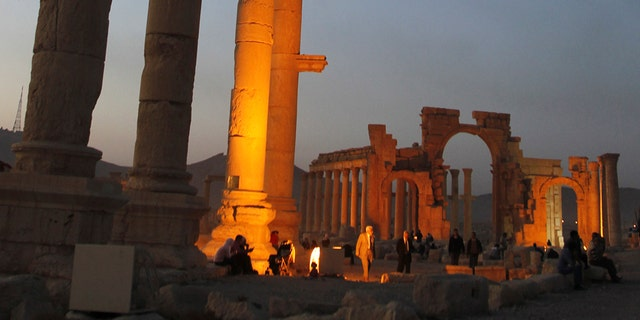 Tourists visit the ruined columns of the historical Palmyra city in the Syrian desert.