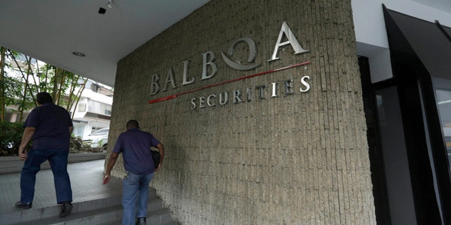 People walk outside the Balboa Bank & Trust Corp. building in Panama City, Thursday, May 5, 2016.