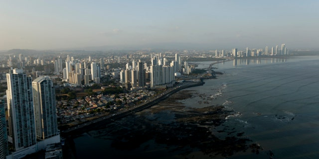 The setting sun lights up the Panama City skyline, Monday, April 4, 2016.