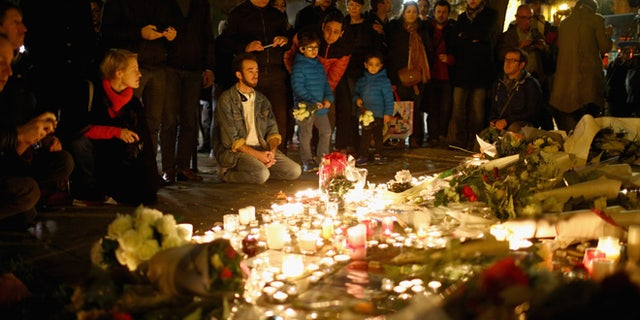 PARIS, FRANCE - NOVEMBER 14:  Flowers and candles are left on the pavement near the scene of yesterday's Bataclan Theatre terrorist attacks on November 14, 2015 in Paris, France. At least 120 people have been killed and over 200 injured, 80 of which seriously, following a series of terrorist attacks in the French capital.  (Photo by Christopher Furlong/Getty Images)