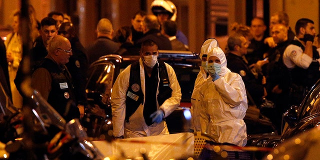 Scientific police officers investigate after a knife attack in central Paris, Saturday.