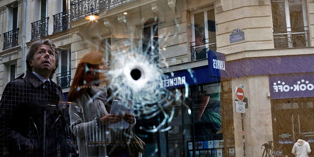 A bullet hole seen on the window of a cafe located near the area where the assailant of a knife attack was shot dead by police officers, in central Paris, Sunday.