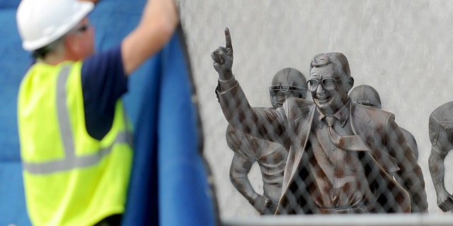 July 22, 2012: Worker hangs a blue tarp over the fence that was installed around the Joe Paterno statue as crews worked to remove the statue in State College, Pa.