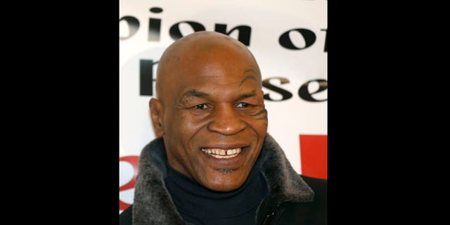 Feb. 16, 2013: File photo, former heavyweight champion Mike Tyson smiles during a promotional event for former five-time champion Evander Holyfield's Real Deal barbecue sauce at a Chicago grocery store.