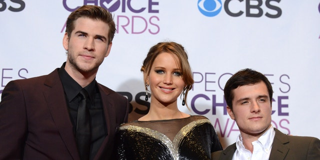 """Jan. 9, 2013:  Liam Hemsworth, Jennifer Lawrence and Josh Hutcherson, winners of the award for best movie for """"The Hunger Games,"""" pose at the People's Choice Awards at the Nokia Theatre."""