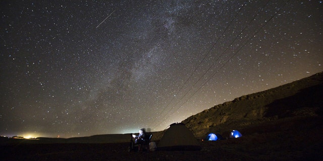A meteor streaks across the sky in the early morning as people watching during the Perseid meteor shower in Ramon Carter near the town of Mitzpe Ramon, southern Israel, Aug.13, 2015.