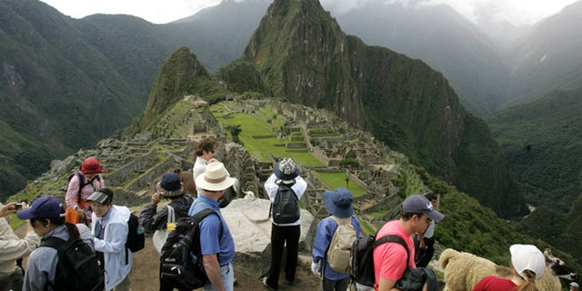 Tourists look at the Inca citadel of Macchu Picchu in Peru. The government is looking to shift some of the tourist burden from Machu Picchu, to Choquequirao, with a plan to build the first aerial tramway that will make Choquequirao reachable in just 15 minutes from the nearest highway.
