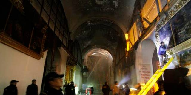 Firefighters and police inspect the famed 16th century San Sebastian church after it was partially destroyed by fire in Cuzco, Peru, Friday, Sept. 16, 2016. The blaze that burned into Friday morning destroyed the ornate, gilded altar and about two dozen paintings at the Temple of San Sebastian. (AP Photo/Percy Hurtado)