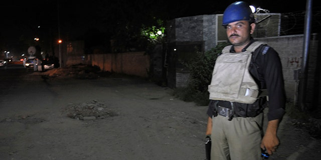 June 25, 2014: A Pakistani police officer stands guard near Peshawar airport which is cordoned off, in Pakistan. Authorities in Pakistan were looking for a gunman who opened fire at a plane Tuesday evening just as it was landing in the volatile northwest, killing one person and wounding two others, officials said, casting fresh doubts about security at the country's airports.