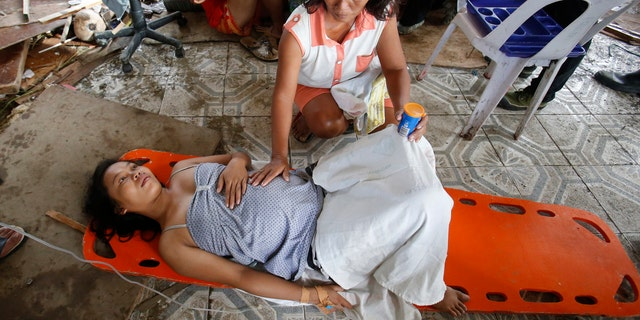 A woman comforts a pregnant relative having labor pains before she delivered a baby at a makeshift birthing clinic in typhoon battered Tacloban city in central Philippines November 11, 2013.