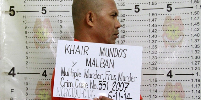June 11, 2014: In this photo released by the Philippine National Police Public Information Office (PNP-PIO) in Manila, Philippines, Khair Mundos, a top commander of the Abu Sayyaf extremist group who is on the U.S. list of most-wanted terrorists and has acknowledged receiving Al Qaeda funds to finance bombings in the country, undergoes a police booking procedure following his capture near Manila's international airport. (AP Photo/Philippine National Police Public Information Office)