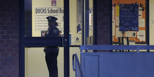 January 17, 2014: Police stands guard the Delaware Valley Charter School in Philadelphia, after two students were shot by another student. (AP)