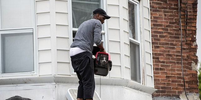 The resident of collapsed home holds his cat on the roof of the standing portion after a Red Paw Emergency Relief Team member rescued his cat on the second floor in Philadelphia, Wednesday, July 26, 2017.