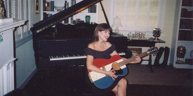 Victoria Hallman holding Buck Owens' guitar.