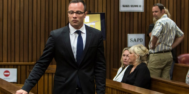 March 17, 2014: Oscar Pistorius, left, walks past June Steenkamp, back left, mother of Reeva Steenkamp, and Jenny Strydom, as he arrives in court in Pretoria, South Africa.