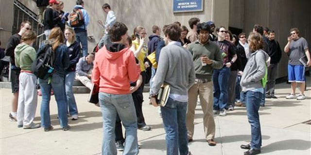April 9: Students wait across the street after being evacuated from buildings adjacent to the University Club on the University of Pittsburgh campus after a bomb threat was received.