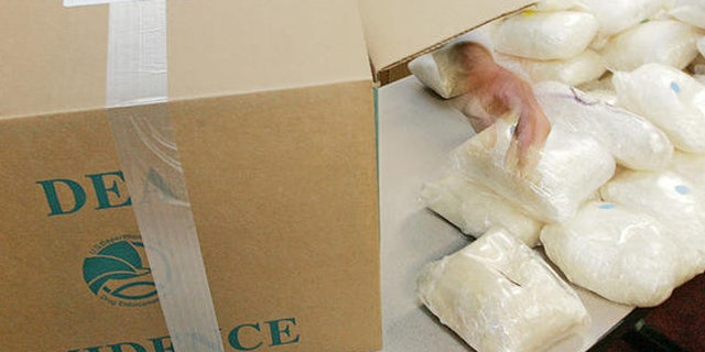 A U.S. Drug Enforcement Administration agent shows some of the 187 plus pounds of methamphetamine  that was seized along with some 41 kilos of cocaine at a house in Gwinnett County on Aug. 16 during a DEA news conference in Atlanta, Monday, Aug. 21, 2006. Four defendants were also arrested and agents recovered a money counter, digital scales, and a large sum of suspected drug proceeds. (AP Photo/Ric Feld)