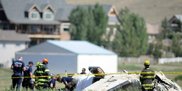 August 31, 2014: Police and firefighters work on the scene where three people were killed and two others injured after an airplane crashed in a field northwest of the main runway at Erie Municipal Airport while coming in for a landing in Erie, Colo. (AP Photo/The Daily Camera, Cliff Grassmick)