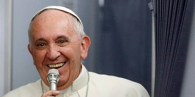 In this photo taken on Sunday, July 12, 2015, Pope Francis smiles as he meets the media during an airborne press conference aboard the airplane directed to Rome, at the end of his Apostolic journey in Ecuador, Bolivia and Paraguay. (AP Photo/Gregorio Borgia)
