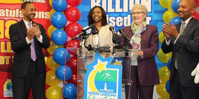In this undated photo provided by the North Carolina Education Lottery, shows Powerball jackpot winner Marie Holmes, second from left, after she received a check from North Carolina Education Lottery executive director Alice Garland, second from right, in Raleigh, N.C. To the left is financial adviser Dexter Perry and attorney Charles Francis, right. (AP Photo/North Carolina Education Lottery)