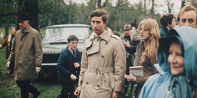 Prince Charles, wearing a belted trench coat, stands with a girlfriend at an outdoor horse event circa 1970. A Range Rover Classic car can be seen in the background. (Photo by Rolls Press/Popperfoto/Getty Images)