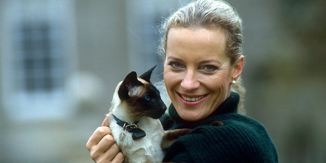 Princess Michael of Kent holds her pet Siamese cat in the gardens of her home, Nether Lypiatt Manor.