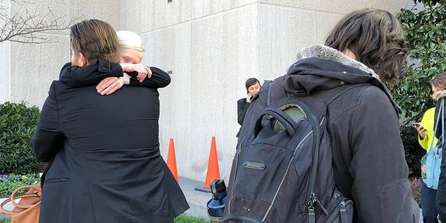 Two acquitted Inauguration Day protesters hug after the verdict's decision.