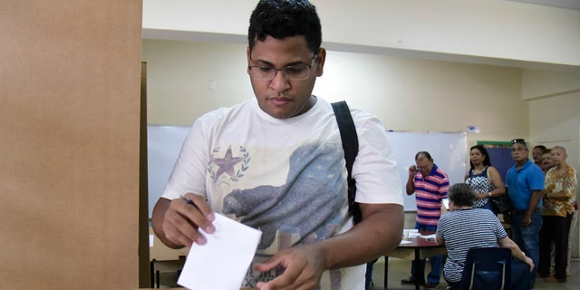 Puerto Rico resident Hector Feliciano votes during the U.S. territory's Democratic primary election at the Luis Llorens Torres Elementary School in San Juan, Puerto Rico, Sunday June 5, 2016 . Puerto Ricans frustrated by island's economic crisis are voting in the U.S. territory's Democratic presidential primary, as front-runner Hillary Clinton draws closer to securing the number of delegates needed to win her party's nomination. (AP Photo/Carlos Giusti)