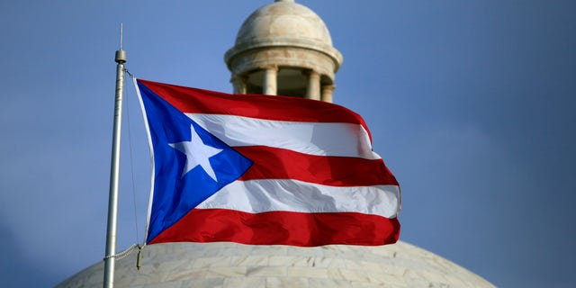 FILE - In this July 29, 2015 file photo, the Puerto Rican flag flies in front of Puerto Rico's Capitol as in San Juan, Puerto Rico. The White House plans to announce the members of a new oversight board to help manage Puerto Rico's debt-stricken economy. Legislation passed in June set up the control board and required the White House to choose from a list recommended by congressional leaders by September. (AP Photo/Ricardo Arduengo, File)