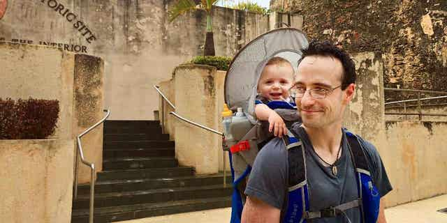 In this May 22, 2015 photo, Elijah Van Benschoten carries his 17-month-old son Hunt Van Benschoten while visiting Castillo de San Cristobal in San Juan, Puerto Rico. No matter how experienced a traveler you are, an overseas trip taken with a baby or toddler requires changes in planning, expectations and itineraries. (Amber Hunt via AP)