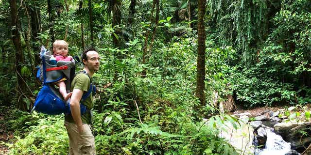 In this May 23, 2015 photo, Elijah Van Benschoten carries his 17-month-old son Hunt Van Benschoten while hiking through El Yunque National Rainforest in Puerto Rico. No matter how experienced a traveler you are, an overseas trip taken with a baby or toddler requires changes in planning, expectations and itineraries. (Amber Hunt via AP)