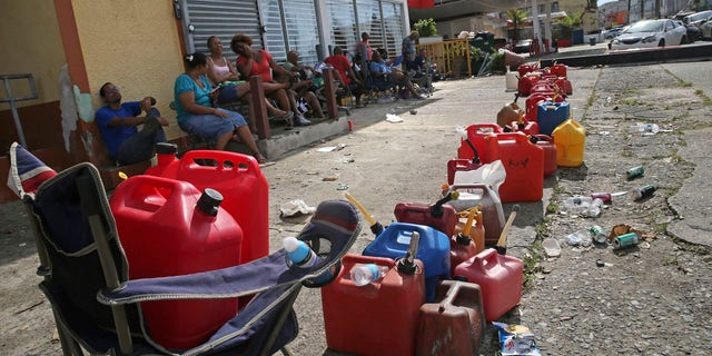 Residents line up gas cans as they wait for a gas truck to service an empty gas station, in the aftermath of Hurricane Maria in Loiza, Puerto Rico.