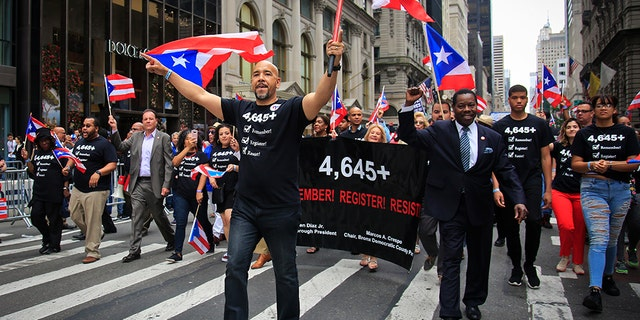 """Bronx Borough President Ruben Diaz, center, leading a group of state and city officials during the Puerto Rican Day Parade. The """"4,645"""" referred to the hurricane's estimated death toll according to a recent Harvard University study, as opposed to the government's official count, 64."""