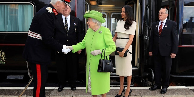Britain's Queen Elizabeth II and Meghan, the Duchess of Sussex, arrive by Royal Train at Runcorn Station, northwest England.