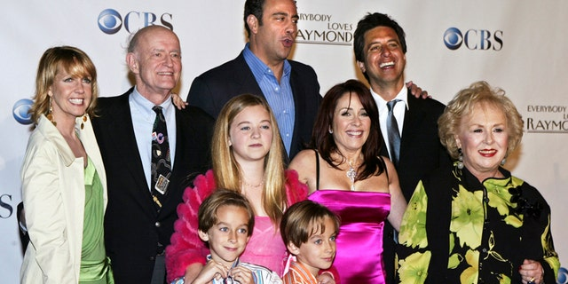 """Cast members of """"Everybody Loves Raymond,"""" (back L-R) Monica Horan, Peter Boyle, Brad Garrett, Ray Romano, (middle L-R) Madylin Sweeten, Patricia Heaton, Doris Roberts, (front L-R) Sawyer Sweeten and Sullivan Sweeten, pose for a group photo at the series wrap party in Santa Monica, California April 28, 2005."""
