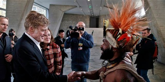 Chief of the Huli tribe in Papua New-Guinea, Mundiya Kepanga, right, shakes hands with actor and environmental activist Robert Redford, prior to a conference on climate, at the UNESCO headquarters, in Paris, Sunday, Dec. 6, 2015.(AP Photo/Thibault Camus)