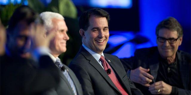 Wednesday, Nov. 19, 2014: Wisconsin Gov. Scott Walker, center; Indiana Gov. Mike Pence, left, and Texas Gov. Rick Perry in Boca Raton, Fla.