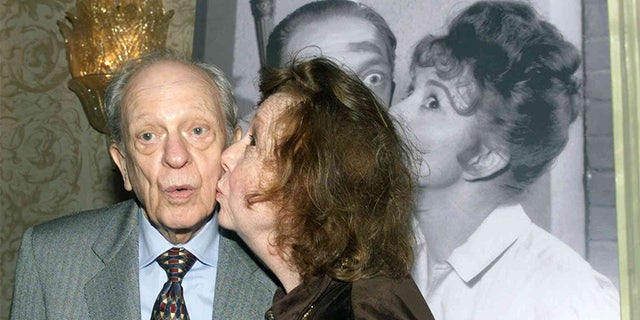 Actor Don Knotts is kissed by actress Betty Lynn who portrayed Fife's girlfriend Thelma as they recreate a pose from a publicity photograph in this January 19, 2000 file photo.