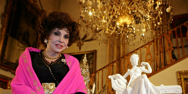 """Italian film icon Gina Lollobrigida poses near one of her marble sculptures in her villa in southern Rome December 7, 2006. Lollobrigida vowed on Thursday to make the media pay for ruining her plans to marry Javier Rigau, a Spaniard 34 years her junior. In an interview with Reuters after she arrived in Rome from Philadelphia, the 79-year-old film star said the couple had called off their wedding plans after Rigau was worn down by """"endless attacks, slander and violence"""" from the media.    REUTERS/Chris Helgren   (ITALY) - GM1DUCNMRLAA"""