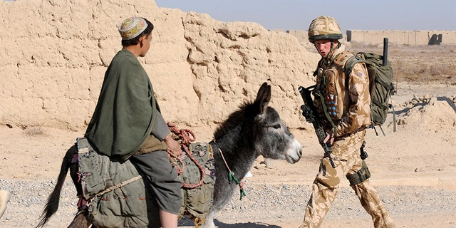 Britain's Prince Harry passes a donkey while on patrol through the deserted town of Garmisir, in Helmand province, southern Afghanistan January 2, 2008.