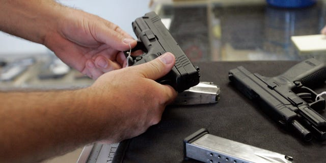 June 26, 2008 file A customer inspects a 9mm handgun at Rink's Gun and Sport in the Chicago, suburb of Lockport, Illinois
