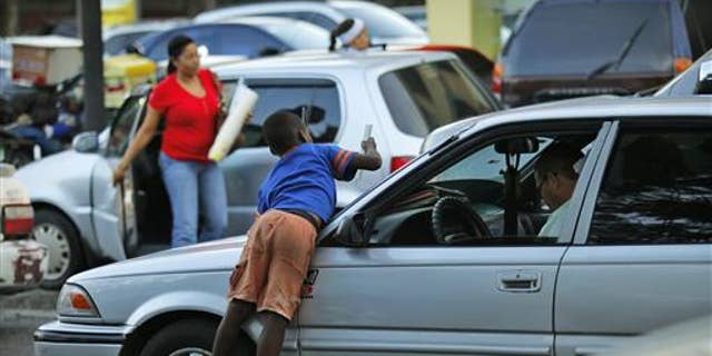 An immigrant child from Haiti cleans the windshield of a car before asking for money on the streets of Santo Domingo June 29, 2011.  REUTERS/Eduardo Munoz (DOMINICAN REPUBLIC - Tags: SOCIETY)