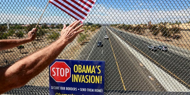 An anti-immigration protester holds a flag and waves to motorists on a highway overpass on Murrieta Hot Springs Blvd in Murrieta, California July 19, 2014. U.S. President Barack Obama will meet with the leaders of Honduras, Guatemala and El Salvador next week to discuss cooperation on the influx of child migrants from Central America into the United States, senior administration officials said on Friday.  REUTERS/Sandy Huffaker  (UNITED STATES - Tags: SOCIETY IMMIGRATION CIVIL UNREST POLITICS) - RTR3ZD18