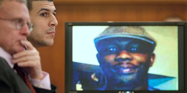Former New England Patriots football player Aaron Hernandez listens during his trial as defense attorney Charles Rankin (L), looks on while an image of Odin Lloyd is displayed on a monitor in Fall River, Massachusetts, January 29, 2015. Hernandez is accused of murdering semi-professional football player Odin Lloyd.