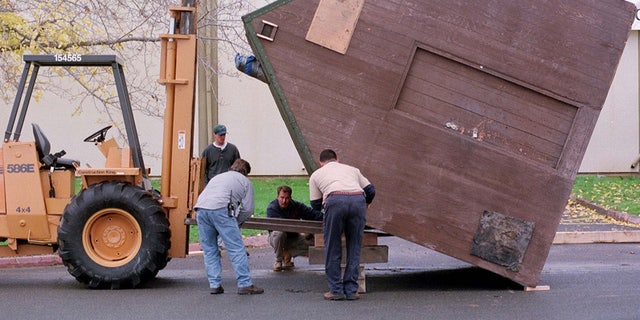 Workers prepare to right the cabin home of Unabomber suspect Theodore Kaczynki on December 5 after it was unloaded from a truck at the former Mather Air Force Base in Rancho Cordova, California. The 10 x 12-foot cabin was moved by truck from Montana by the defense to exhibit to jurors during the upcoming trial.UNABOMBER - RTR9DCZ