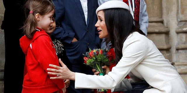 Britain's Prince Harry's fiancee Meghan Markle receives a bouquet of flowers.